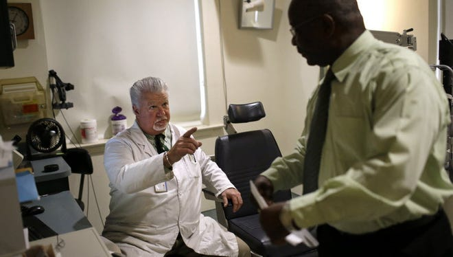In this March 12, 2015 photo, optometrist Paul Archambault, left, speaks with U.S. Army veteran William White after performing a glaucoma examination on White at the Fayetteville Veterans Affairs Medical Center in Fayetteville, N.C.