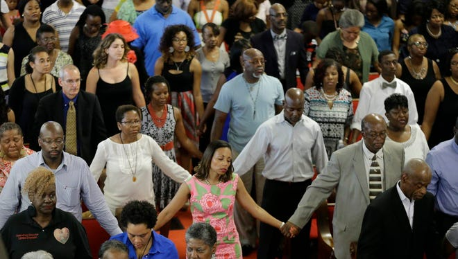 Congregants link hands as they sing inside the Emanuel African Methodist Episcopal Church in Charleston, S.C., Sunday.