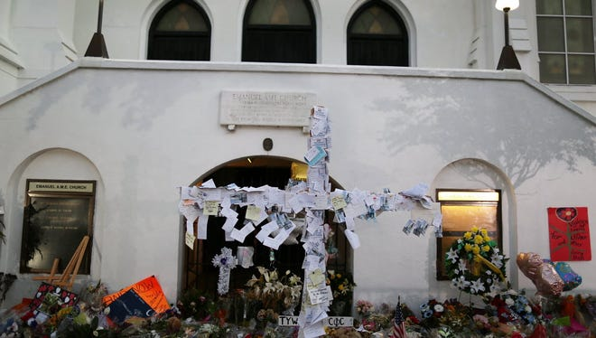 A cross is seen adorned with messages at a memorial in front of the Emanuel African Methodist Episcopal Church on June 22, 2015. A mass shooting June 17 at the church killed nine people.