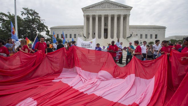 Supporters of gay marriage unfurl an equality flag outside the Supreme Court, before the justices handed down the gay marriage decision.