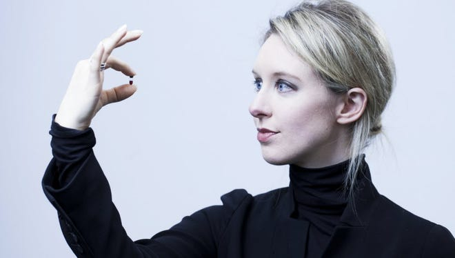 Theranos founder Elizabeth Holmes holds one of her bloodwork company's FDA-approved Nanotainers, where mere drops of blood are stored for complex tests.