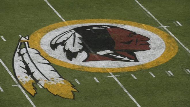 The Washington Redskins logo is seen on the field before an NFL football preseason game in 2014.