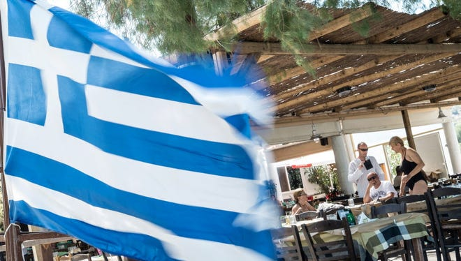 """People sit in a restaurant next to a Greek flag on the Salamina island near Athens, on July 12, 2015. Greece can reach a bailout deal on July 12 with its European creditors if all sides try, Greek Prime Minister Alexis Tsipras said as he arrived for a eurozone summit facing deep divisions. """"I'm here for an honest compromise. We owe that to the people of Europe. We can reach an agreement tonight if all parties want it,"""" Tsipras told reporters in Brussels."""