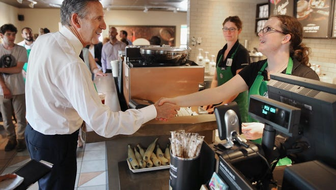Starbucks CEO Howard Schultz greets employees and others at the coffee shop around the corner from the historic Emanuel African Methodist Episcopal Church June 19, 2015, in Charleston, S.C. Schultz and a coalition of executives are set to launch a campaign Monday to hire 100,000 young people who aren't in school or employed.