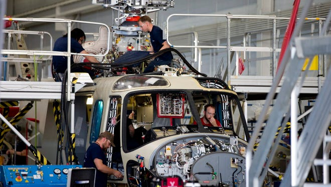 Workers help to assemble a helicopter on June 22, 2015, in Philadelphia.