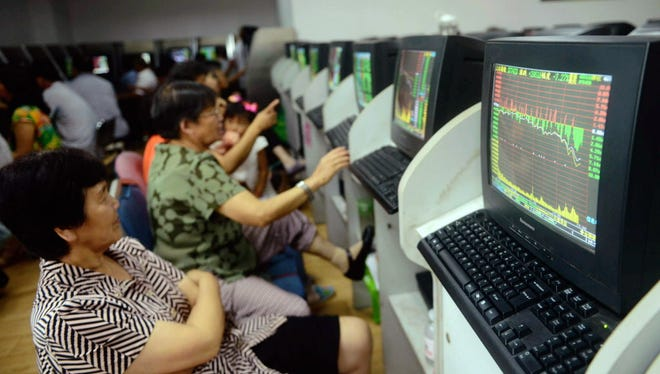 In this photo provided by China's Xinhua News Agency, people pay attention to stock market quotation at a business lobby of a security company in Qingdao, east China's Shandong Province, Monday, July 27, 2015.  The Shanghai share index dived more than 8 percent Monday as Chinese stocks suffered a renewed sell-off despite government efforts to calm the market. (Yu Fangping/Xinhua News Agency via AP) NO SALES ORG XMIT: XIN801
