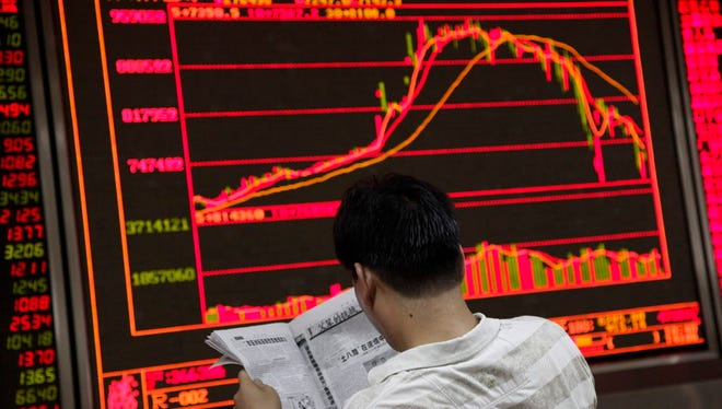 An investor reads a newspaper as an electronic board shows stock market data in Beijing on July 29, 2015.