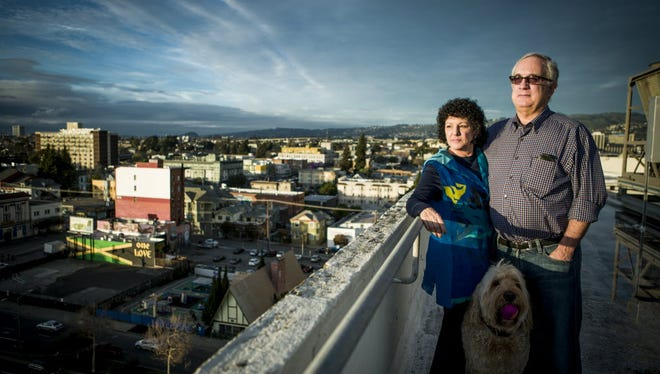 Mitch and Freada Kapor pose for photos with their dog Dudley on the roof of the downtown Oakland, Calif., offices of The Kapor Center for Social Impact on Monday, December 8, 2014.
