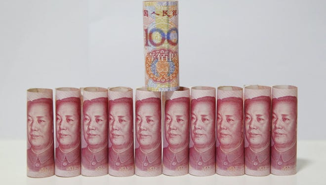 Chinese 100 yuan notes are arranged for a photograph in Beijing on August 12.