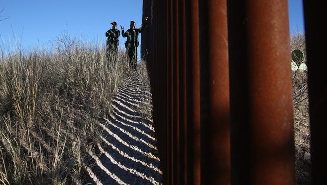 Border Patrol agents at the fence in Nogales, Ariz.
