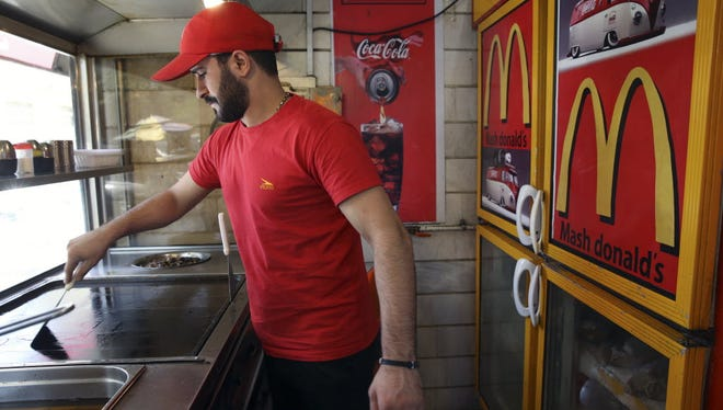 """Iranian worker at a """"Mash Donald's"""" fast-food restaurant in Tehran on Aug. 5, 2015."""