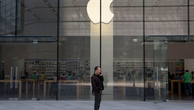 In this April 22, 2014 file photo, a man uses his phone near an Apple store in Beijing.
