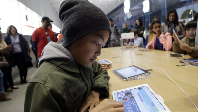 Tyson Navarro, 10, of Fremont, Calif., learns to build code using an iPad at a youth workshop at the Apple store in 2013.  Code.org said a record number of female and under-represented minority students took AP computer science classes in 2018.