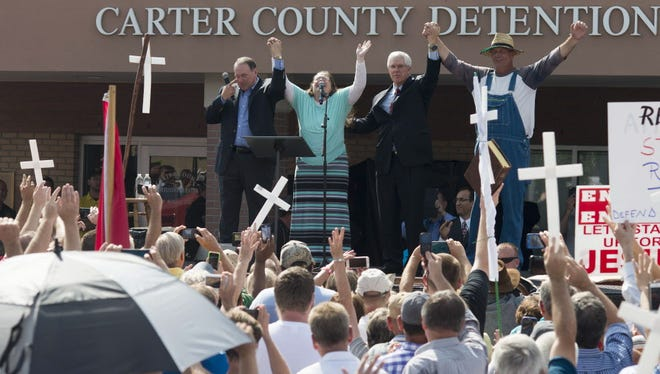 Rowan County Clerk of Courts Kim Davis (second from left) joins hands with her attorney Mat Staver (second from right), husband Joe Davis (right) and Republican presidential candidate Mike Huckabee in front of the Carter County Detention Center on Sept. 8, 2015 in Grayson, Ky.