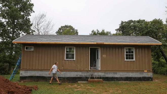 This cargo container home has a traditional gable roof and a dark hue to blend with rural neighbors in Upton, Ky.  Built by the Hardin County Habitat for Humanity for $30,000, half the cost of a traditional Habitat project, this home nonetheless is the last of its kind as neighboring communities fear impact on property values.  Sept. 10, 2015