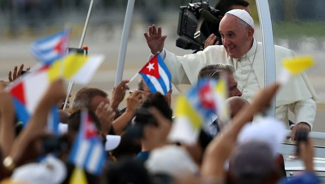 People wave Cuban and papal flags as Pope Francis passes by in Havana on Sept. 20, 2015.