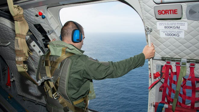 In this photo released Aug. 7, 2015, by the French Army Communications Audiovisual office, a crewmember looks out the door of a CASA 235 plane from the 181st Air Detachment of the French Air Force taking part in the search for wreckage from missing Malaysia Airlines Flight 370 off the coast of the French island of La Reunion.