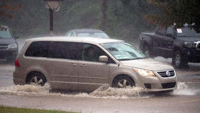 Traffic moves along Patton Avenue during heavy rainfall Tuesday afternoon. More rain is expected this weekend, with the chance for flash flooding in Western North Carolina.