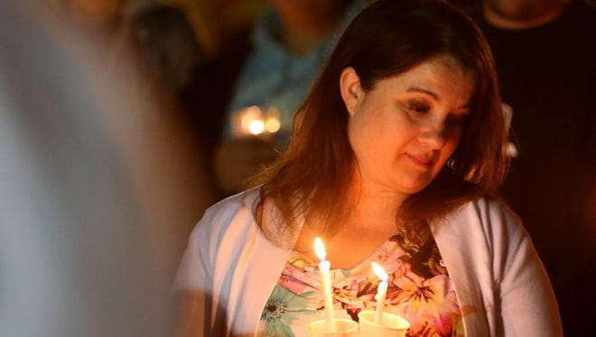 Nicole Norton, 40, of Roseburg, attends a vigil at Stewart Park in Roseburg, Ore., on Thursday, Oct. 1, 2015.