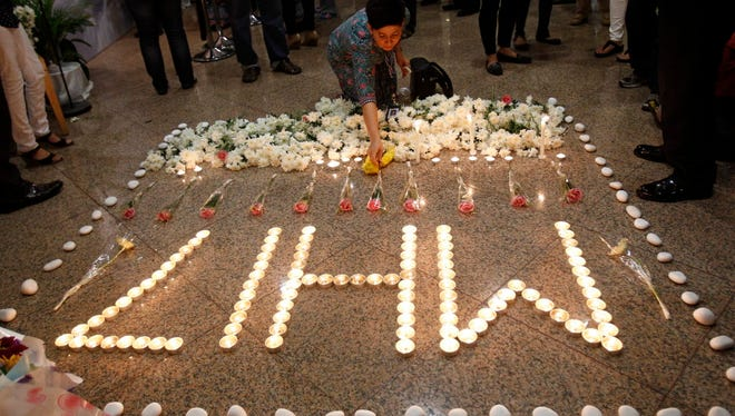 In this July 25, 2014 file photo, a Malaysia Airlines crew member places a flower next to candles forming the letters MH17 after a multi-faith prayers for the victims of the downed Malaysia Airlines Flight 17 at Malaysia Airlines Academy in Kelana Jaya, near Kuala Lumpur, Malaysia.