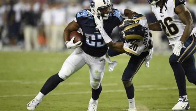 Titans rookie running back David Cobb tries to get past a couple of Rams during a preseason game at Nissan Stadium.