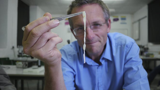 """In this undated picture provided by BBC Worldwide, presenter Michael Mosley from """"BBC Earth"""" holds up an adult beef tapeworm on the program."""