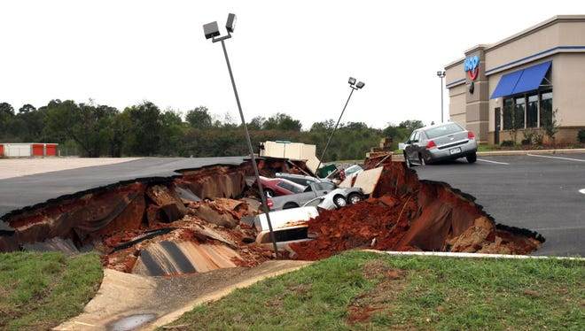Vehicles fell into a hole that opened Nov. 7, 2015, in a restaurant parking lot in Meridian, Miss.