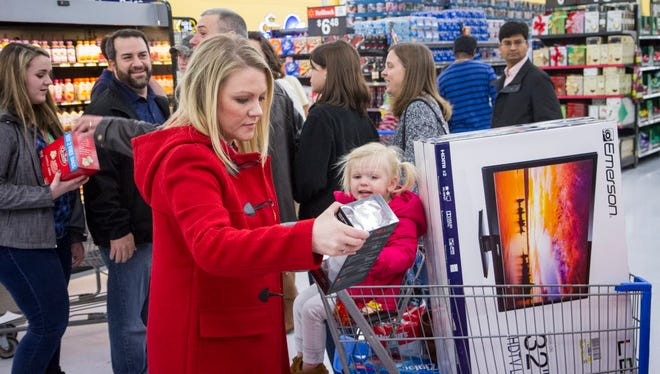 "Liz Richardson, left, and her daughter Aubrey, 2, fill their cart with a 32"" TV, diapers, and a portable speaker among other items during Black Friday shopping on Thursday, Nov. 27, 2014 in Bentonville, Ark."