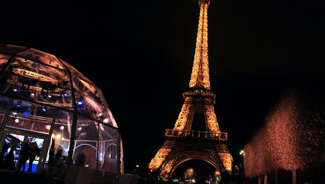 An image of the Eiffel Tower lit up on Nov. 13, 2015, before the deadly Paris attacks. Its lights were extinguished in honor of those who died.