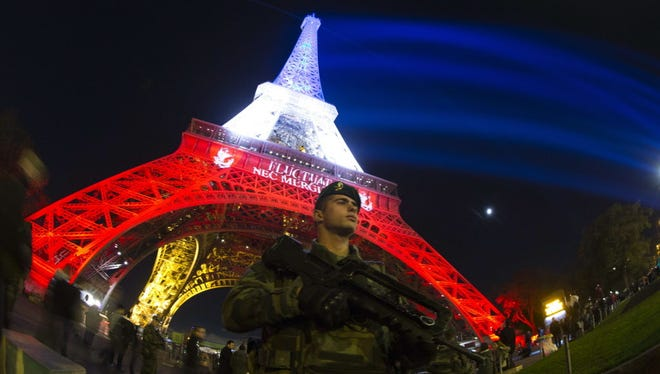 A soldier patrols in Paris Nov. 18 in front of the Eiffel Tower, which is illuminated with the colors of the French flag in tribute to the victims of the Nov.13 terror attacks.