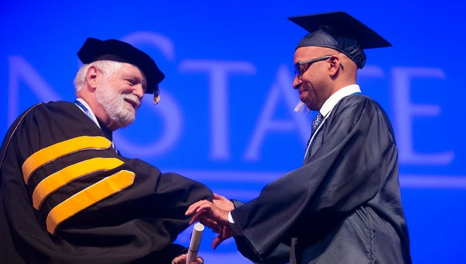Penn State York Chancellor David Chown hands a diploma to a graduate during the spring 2015 commencement ceremony.