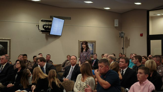 Alisha Wilson stands to accept her Governor's Shine Award on Tuesday during Florida's Cabinet meeting in Tallahassee.