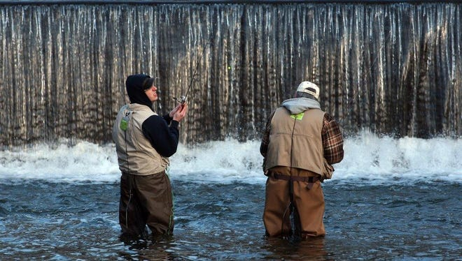 Fishermen at Speedwell Lake in Morristown cast their lines on the opening day of New Jersey's trout season in April. Both anglers display their freshwater licenses on their backs in green.