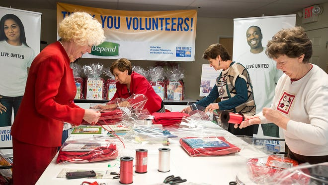 (From left) Incoming Chair of United Way's Women's Leadership Initiative Wendy Bartlett of Ventnor wraps blankets and books with members Dee Kassis of Absecon, Deb Davies of Absecon and Beverly Gilbert of Somers Point. The gifts were distributed to local families in need as part of Project Heart-to-Heart, an initiative of United Way's All Wrapped Up holiday giving program.