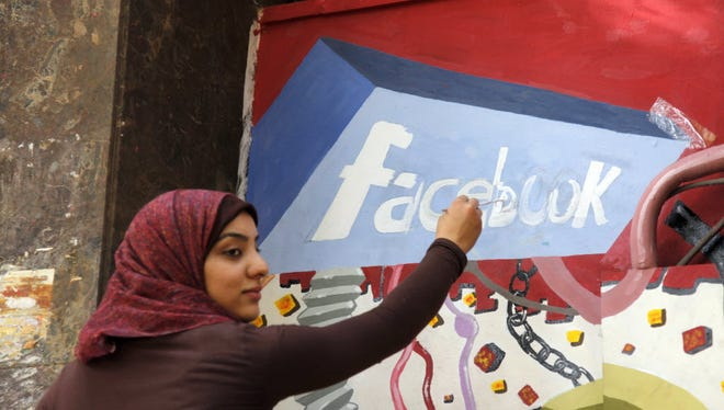 In this March 30, 2011 file photo. an art student from the University of Helwan paints the Facebook logo on a mural commemorating the revolution that overthrew Hosni Mubarak in the Zamalek neighborhood of Cairo, Egypt. In a statement to The Associated Press on Wednesday, Facebook said it is disappointed that a program providing free basic Internet services to over three million Egyptians has been shut down.