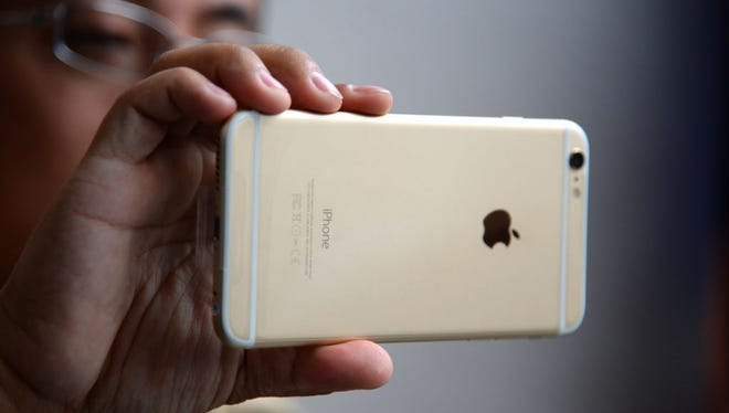 This September 19, 2014 file photo shows a man as he looks at his  iPhone 6 Plus outside the Apple store in Pasadena, California.