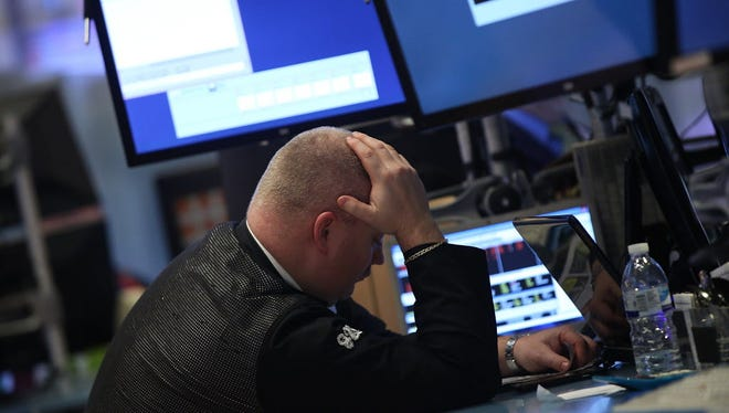 Traders work on the floor of the New York Stock Exchange (NYSE) at the end of the day on January 15, 2016 in New York City.