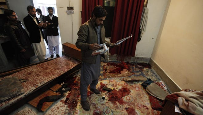 Students inspect a bloody room after a Taliban attack on Bacha Khan University in  Pakistan on Jan. 20, 2016.