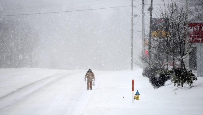 A man walks in tire tracks in the road because the sidewalks were covered as he makes his way down New Leicester Highway in the snow on Friday.