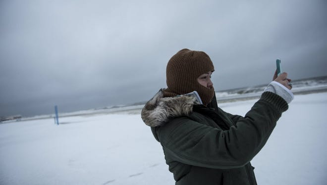 Colie Brooks, 19, from North Cape May, takes a picture on the beach on January 23, 2016 in Cape May New Jersey. A major snowstorm is upon the East Coast this weekend with some areas expected to receive over a foot of snow.