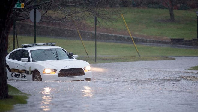 A Buncombe County Sheriff's Office car backs up from a flooded Lakeshore Drive as rain pounds the area Wednesday morning.