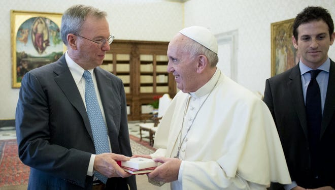 Eric Schmidt, executive chairman of Alphabet, left, exchanges gifts with Pope Francis during an audience in the pontiff's studio at the Vatican in January.
