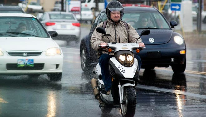 A man drive a moped through the rain on Tunnel Road as fast moving storms continue to pass through Western North Carolina.