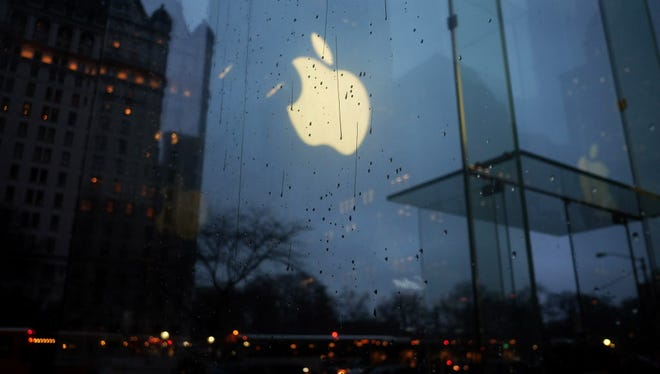 The Apple logo is seen reflected on the glass of its store on Fifth Avenue in New York on February 23, 2016.