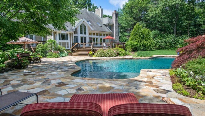 This five-bedroom estate home in the Mendham Lakes community in Randolph  has an in-ground pool and an outdoor grill kitchen, an updated indoor kitchen with a center island, and a library.