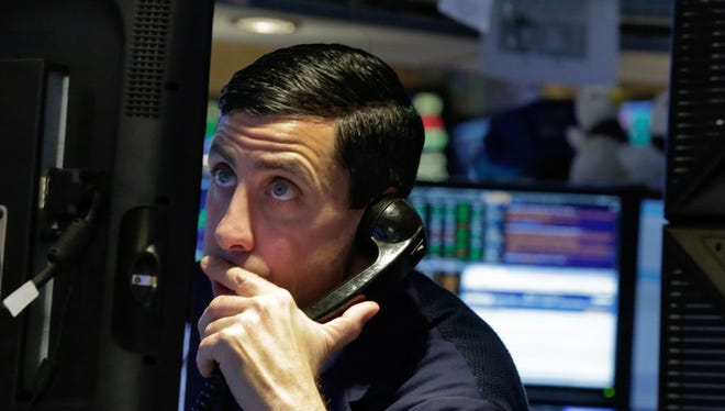 A trader studies his screen as he works on the floor of the New York Stock Exchange, Wednesday, March 30, 2016.