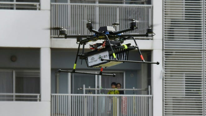 A drone developed by Japan's Autonomous Control Systems Laboratory (ACSL) flies beside a condomimium for a field test in Chiba, suburb of Tokyo, on April 11, 2016.