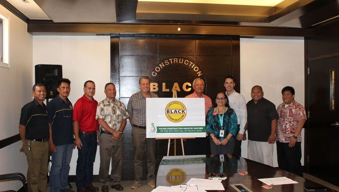 Black Construction Corp. officials and Festival of Pacific Arts officials pose next to a sign announcing the company as a major construction industry partner for FestPac.