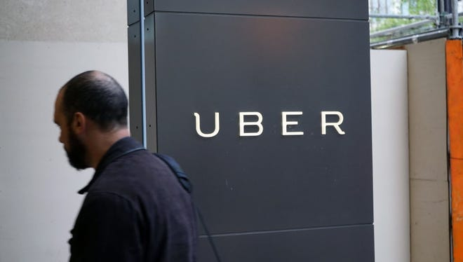 A man walks past the sign for the Uber headquarters in downtown San Francisco.