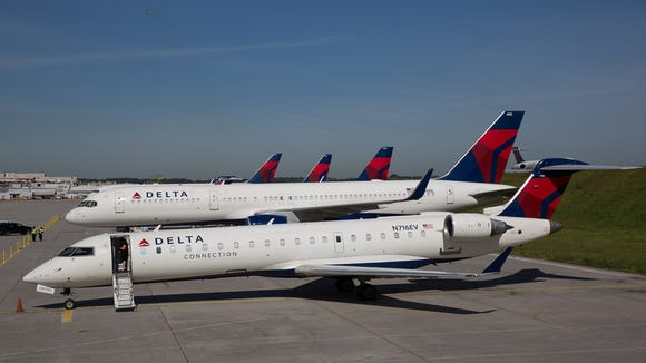 Several Delta Air Lines jets rest outside a hangar